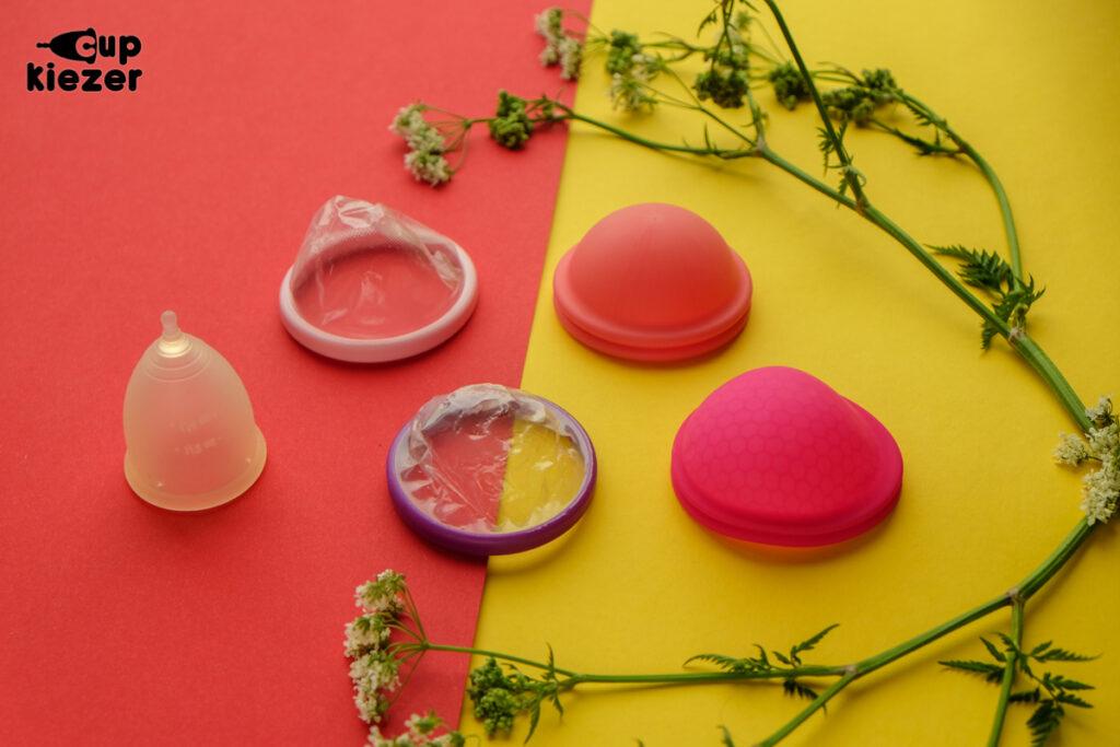 Menstruatiecup naast twee wegwerp menstruatiedisks en twee herbruikbare menstruatiedisks (Nixit en ziggy)